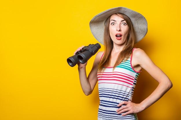 Женщина в шоке, удивленная, в шляпе и полосатом платье держит бинокль на желтом пространстве.