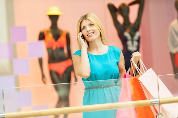 Женщина в торговом центре. красивая зрелая женщина держит сумки и разговаривает по мобильному телефону, стоя в торговом центре