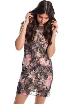 Женщина в коротком темном платье. платье с розовым цветочным принтом. модное платье от известного бренда. мягкая подкладка из шелка.