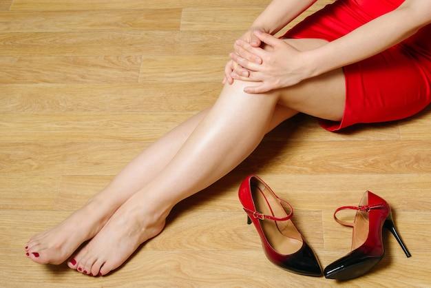 短い赤いドレスを着た女性がかかとのある靴なしで床に座って膝に手を組む