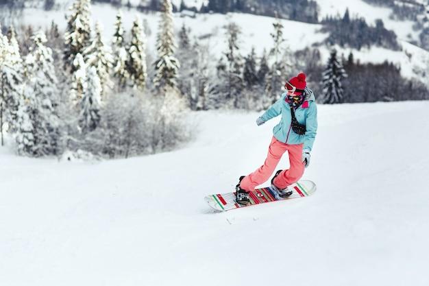 스키 복에 여자는 그녀의 스노우 보드에 언덕을 내려가는 그녀의 어깨 너머로 보인다