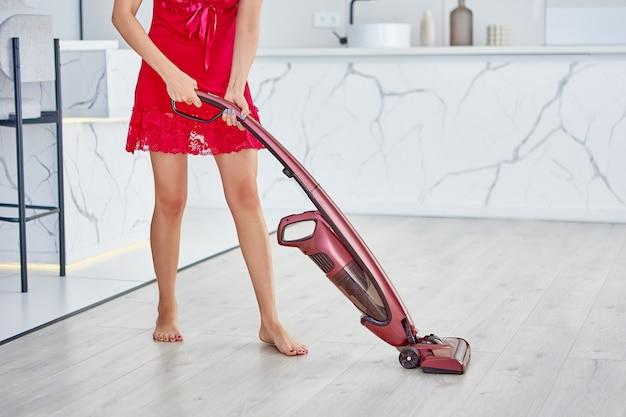 잠옷을 입은 여성이 진공 청소기로 아파트를 청소합니다.