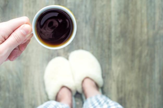 スリッパを履いた女性が一杯のコーヒーを手に持っています。