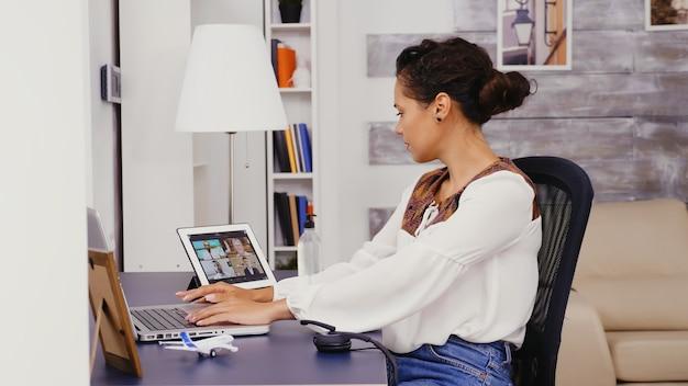 동료와 태블릿 컴퓨터에서 화상 통화를 하는 동안 노트북으로 슬로우 모션을 하는 여성.