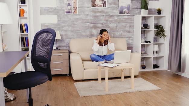 Женщина в замедленном движении, надевая наушники во время видеозвонка, работая из дома.