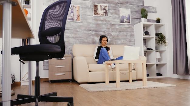 Женщина в замедленном движении разговаривает во время видеозвонка с помощью наушников с микрофоном, работающим из дома.