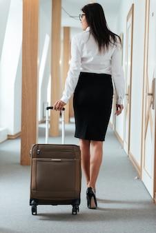 Женщина в нарядной одежде, прогуливаясь по лобби отеля с чемоданом
