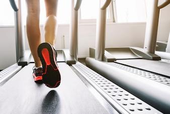 Женщина в кроссовках, бегущих по беговой дорожке
