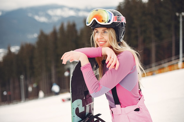 스노우 보드 정장에 여자입니다. 수평선에 손에 스노우 보드와 산에 sportswoman. 스포츠 개념