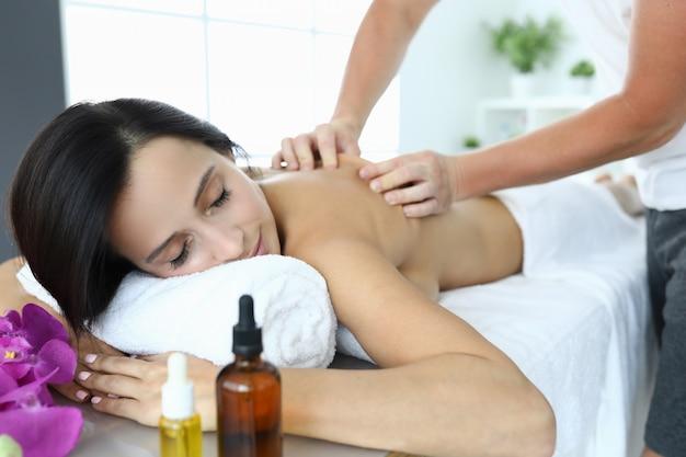 Женщина в спа-салоне получает массаж от массажиста. классический расслабляющий расслабляющий массаж в салоне красоты