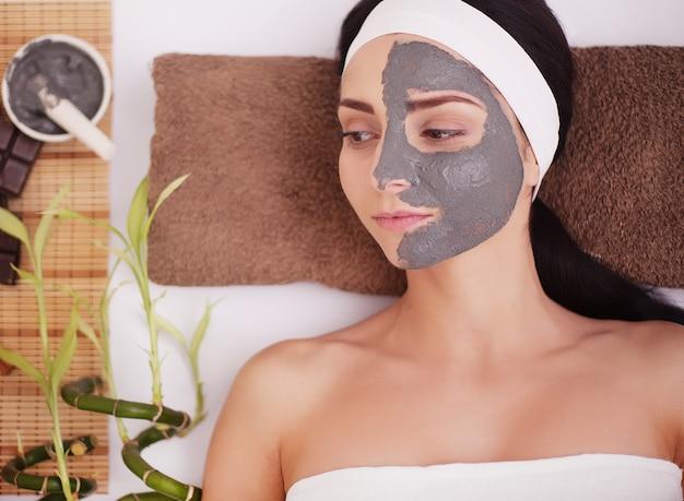 フェイスマスク付きのスパサロンでの女性