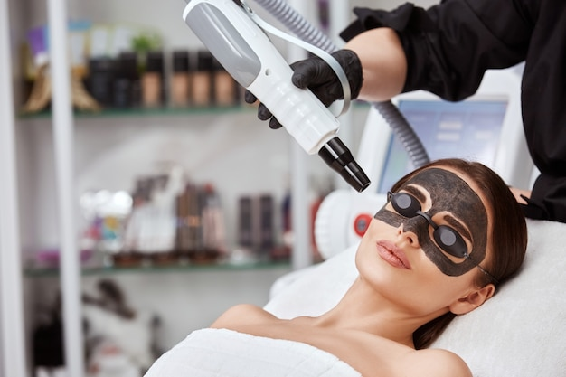 Женщина в спа с черной угольной маской и косметолог с лазером возле лица, копией пространства, милая женщина, омолаживающая косметологом