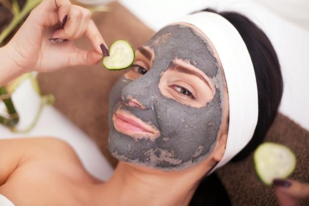 顔にマスクを持つスパの女性