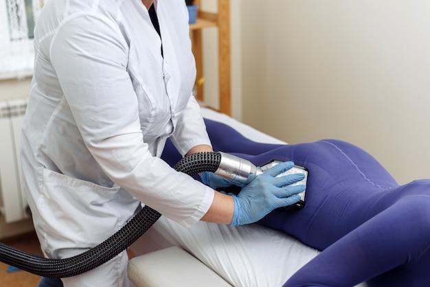 Женщина в специальном фиолетовом костюме получает антицеллюлитный массаж в спа-салоне. процедура массажа lpg. руки терапевта, держащего инструмент для липомассажа.
