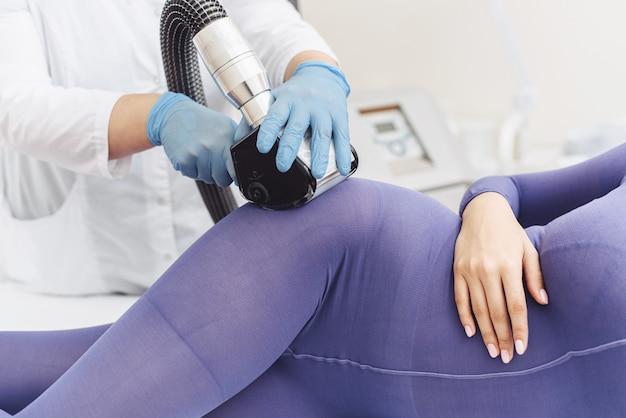 スパサロンでアンチセルライトマッサージを受ける特別な紫色のスーツを着た女性。 lpgマッサージ手順。