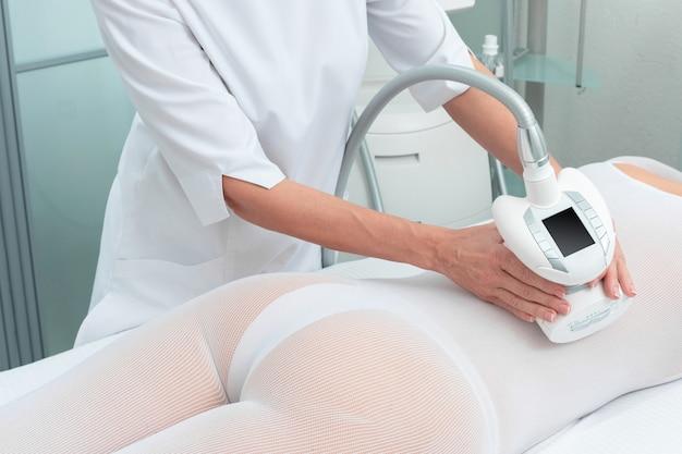 Женщина в специальном белом костюме получает антицеллюлитный массаж в спа салоне. сжиженный газ и контурная обработка тела в клинике.