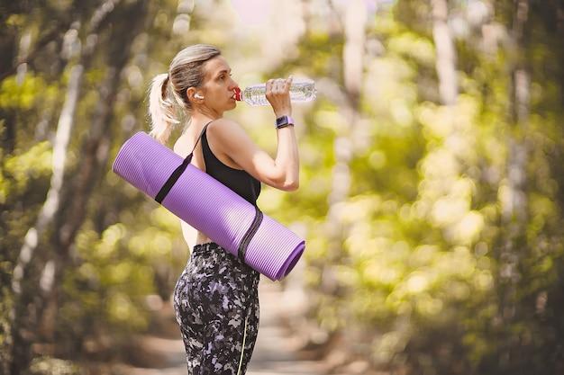 요가 매트를 들고 운동 후 플라스틱 병에서 물을 마시는 스포츠 옷 여자.