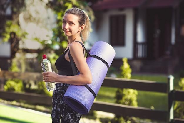 Женщина в спортивной одежде держит коврик для йоги и бутылку с водой после тренировки.