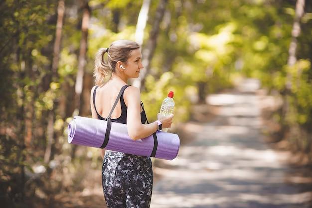 운동 후 요가 매트와 물병을 들고 스포츠 옷 여자.