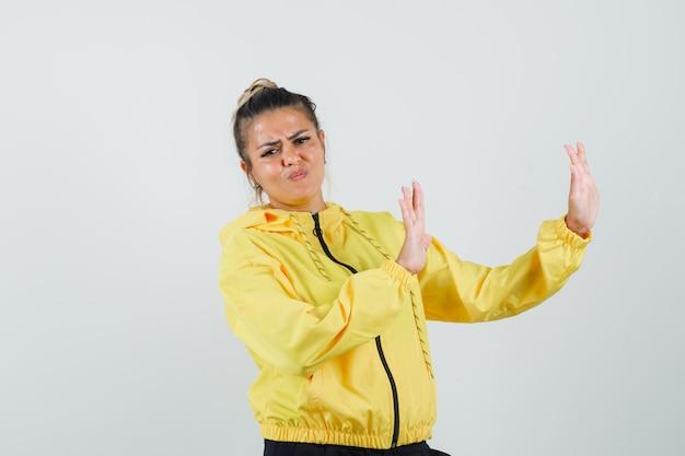Женщина в спортивном костюме, отвергая руки и выглядя раздраженной, вид спереди. Бесплатные Фотографии