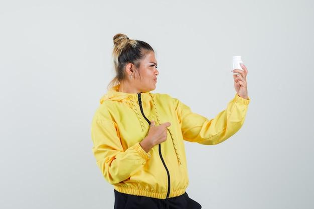 Женщина в спортивном костюме, глядя на бутылку таблеток и глядя сосредоточенно, вид спереди.