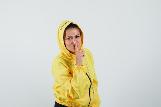 沈黙のジェスチャーを示し、注意深く見ているスポーツスーツの女性、正面図。