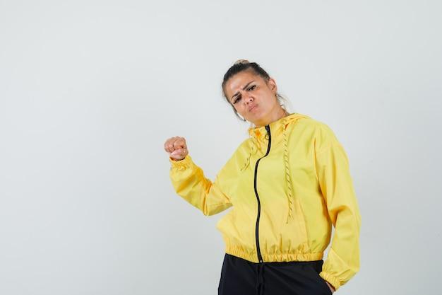 주먹으로 위협하고 화가, 전면보기를 찾고 스포츠 정장에 여자.