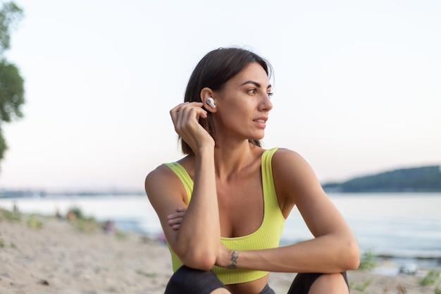 ワイヤレスヘッドフォンで音楽を聴いてトレーニング後に休んでいる都市のビーチで日没時にスポーツウェアの女性