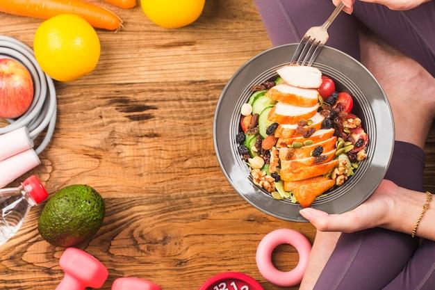 健康的なライフスタイル、健康的な食品を食べる女性と新鮮なサラダの皿を保持しているスポーツウェアの女性