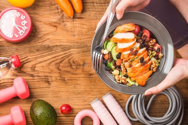 Женщина в спортивной одежде, держащая блюдо из свежего салата, здоровый образ жизни, женщина ест здоровую пищу
