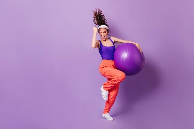스포츠 모자와 밝은 탑을 입은 여성이 승리를 기뻐합니다.
