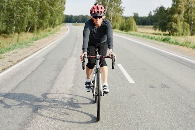 Женщина в спортивной одежде и шлеме катается по дороге на горном велосипеде