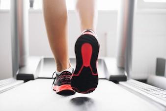 Женщина в спортивной обуви работает на беговой дорожке