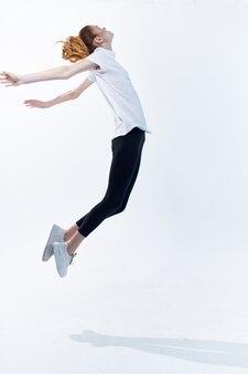 明るい背景をジャンプするスポーツ制服ビッグエネルギーライフスタイルの女性。高品質の写真