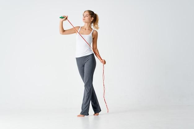 スポーツユニフォーム縄跳びの女性の手のトレーニング運動明るい背景