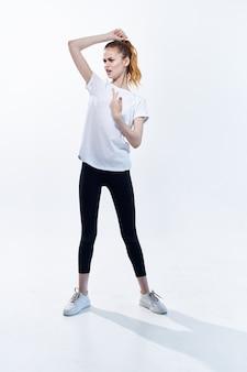 スポーツユニフォームトレーニングポーズフィットネスライト背景の女性