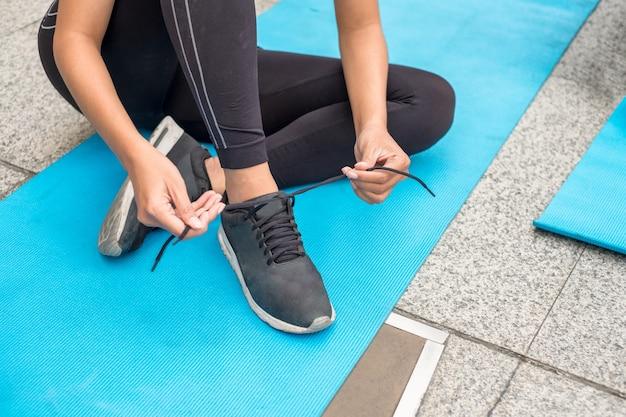 スポーツウェアの女性は青いマットの上に座っているネクタイの靴紐を着用します