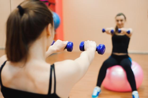 スポーツウェアの女性、フィットボールとダンベルでフィットネス運動を行います。