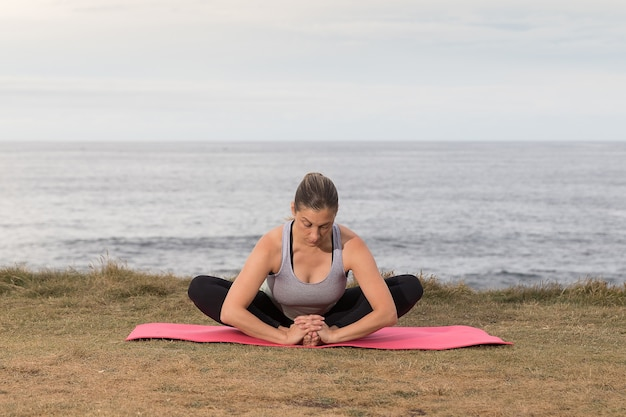 海とピンクのマットで屋外運動スポーツウェアの女性