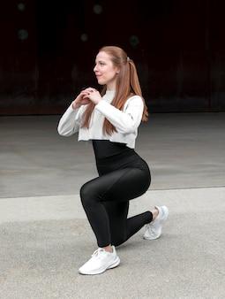Женщина в спортивной одежде, упражнения на открытом воздухе