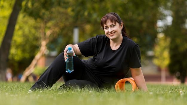 Женщина в спортивной одежде держит бутылку воды