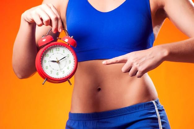 Женщина в спортивной одежде, холдинг будильник. концепция людей, фитнеса и диеты