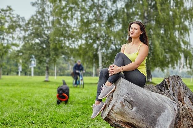 검은 briard가 장난감을 가지고 노는 동안 스포츠웨어에 여자는 공공 공원에 앉아있다.