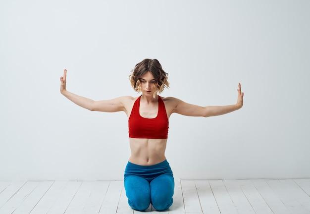 彼女の手ヨガアサナで軽いジェスチャーでスポーツウェアの女性。