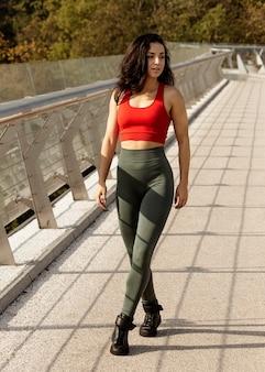 Женщина в спортивной одежде позирует на открытом воздухе