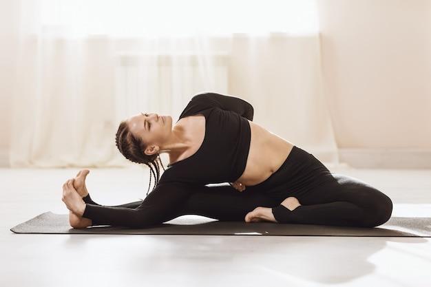 マットの上に座ってヨガを練習しているスポーツウェアの女性は、parivrtta janushirshasana運動の頭膝の姿勢を実行します