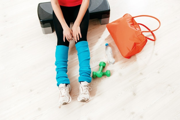 Женщина в спортивной одежде отдыхает в тренажерном зале после тренировки