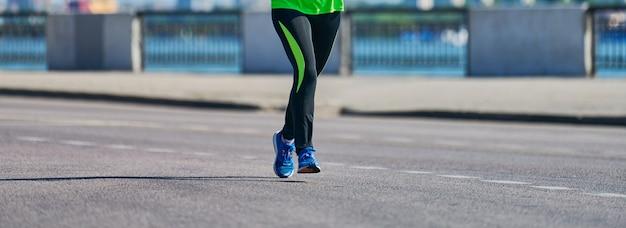 通りを走っているスポーツウェアの女性