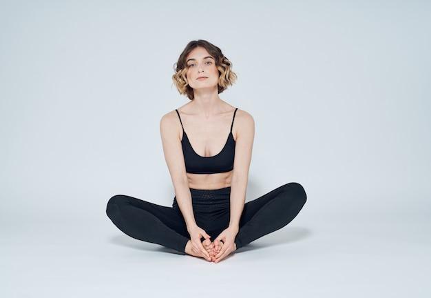 운동복에 여자는 밝은 방과 tshirt에서 바닥에 앉아