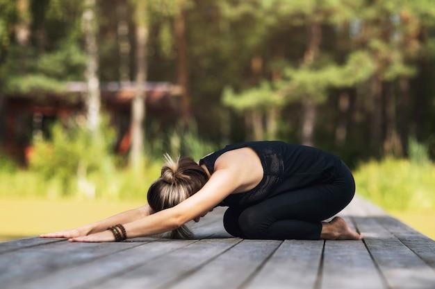 木製の橋の上に座っているスポーツウェアの女性は、子供のポーズを実行するヨガのアーサナを練習します